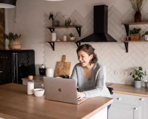 En glad kvinna som surfar hemma
