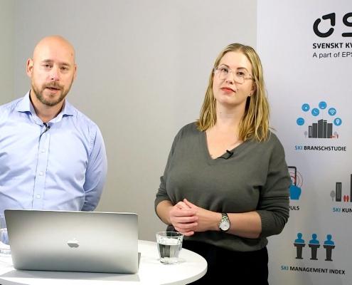 Skärmdump från webinar. Johan och Laurina står vid en dator fram en rollup.