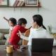 Mamma som försöker arbeta hemma. Barnen leker i bakgrunden.