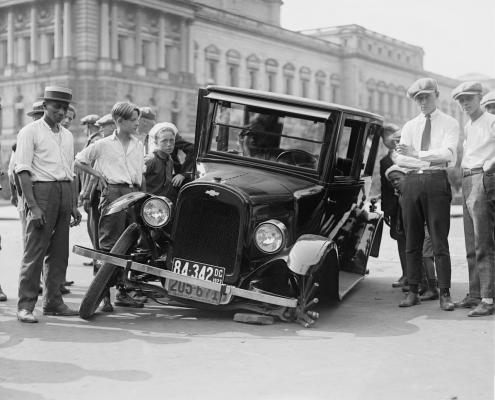 Några män står runt en trasig bil, tidigt 1900-tal